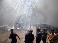 Palestinian demonstrators run from tear gas fired by Israeli troops